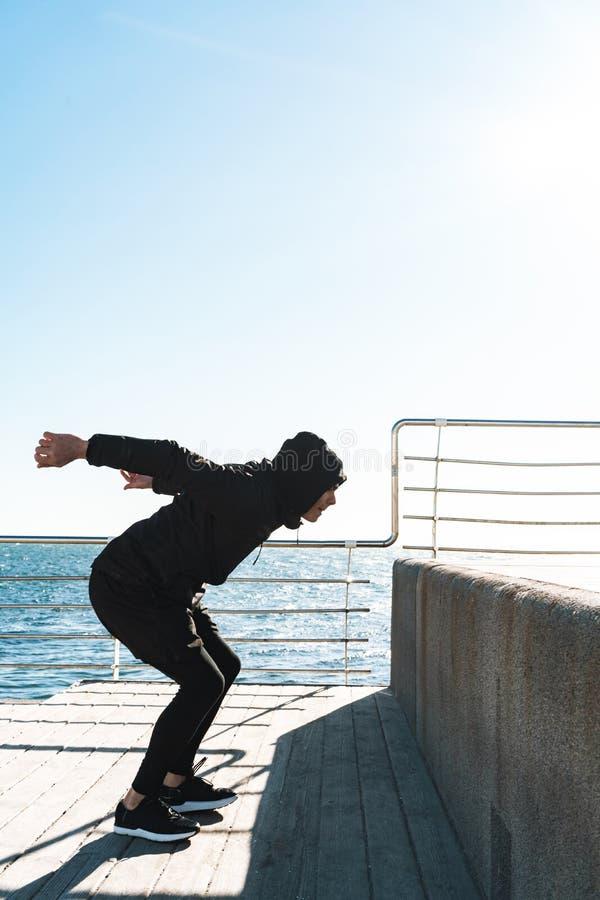 Foto del hombre del parkour que hace la acrobacia y que salta durante entrenamiento de la mañana por la playa imagen de archivo