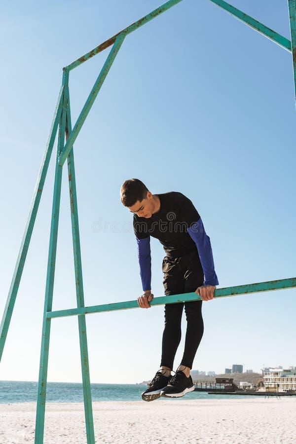 Foto del individuo activo que hace la acrobacia en barra gimnástica horizontal durante entrenamiento de la mañana por la playa fotografía de archivo