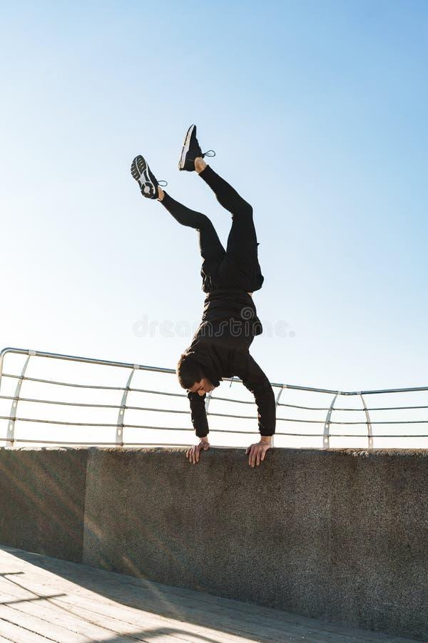 Foto del individuo activo que hace la acrobacia y que salta durante entrenamiento de la mañana por la playa fotos de archivo libres de regalías