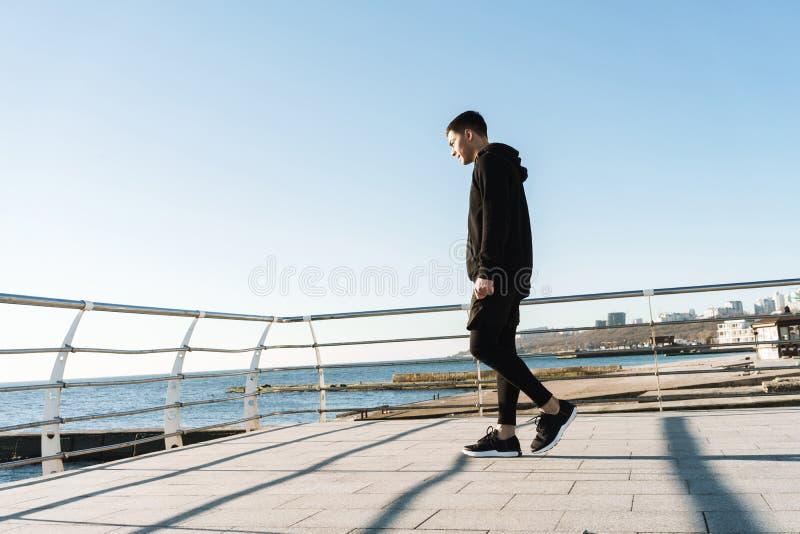 Foto del individuo alegre 20s que camina a lo largo de paseo marítimo de madera por la playa después de entrenamiento de la mañan imagen de archivo