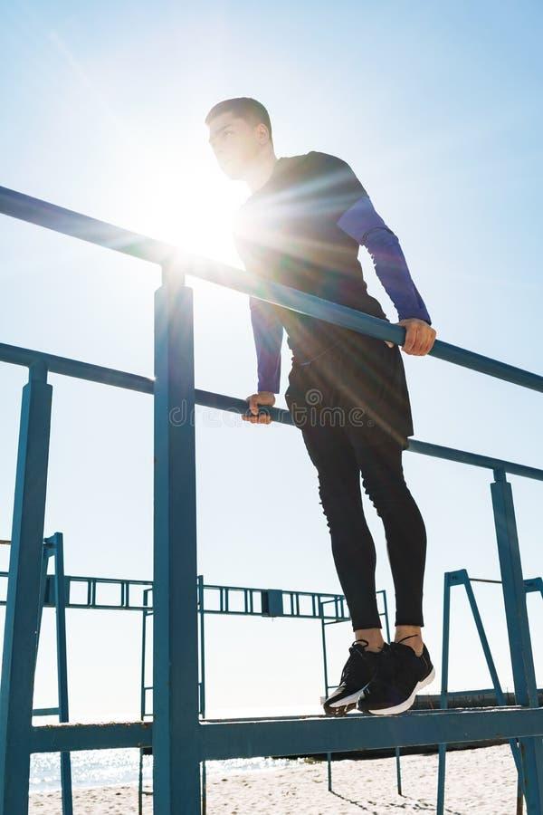Foto del individuo atlético que hace la acrobacia en barra gimnástica horizontal durante entrenamiento de la mañana por la playa fotos de archivo libres de regalías
