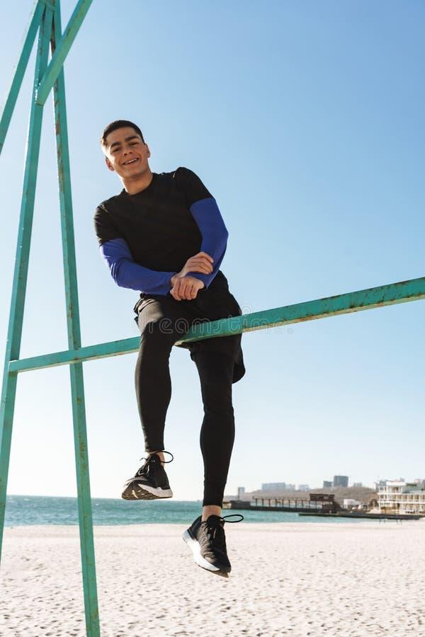 Foto del individuo atractivo que hace la acrobacia en barra gimnástica horizontal durante entrenamiento de la mañana por la playa fotografía de archivo libre de regalías