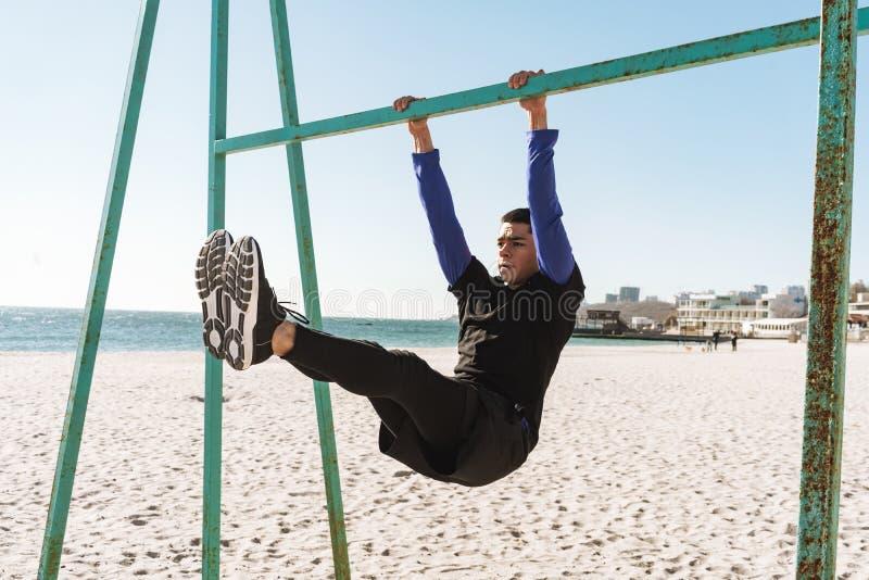 Foto del individuo caucásico que hace la acrobacia en barra gimnástica horizontal durante entrenamiento de la mañana por la playa imagen de archivo