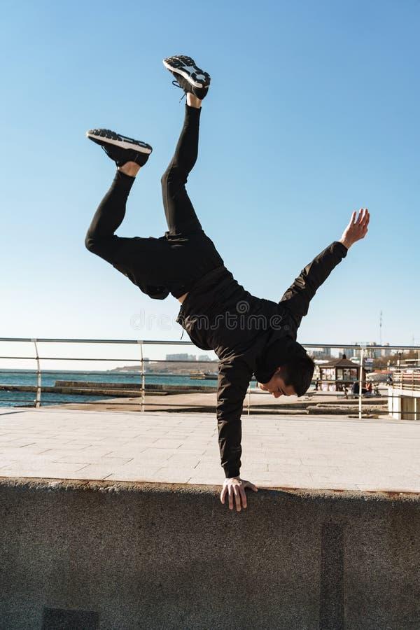 Foto del individuo europeo que hace la acrobacia y que defiende en sus brazos durante entrenamiento de la mañana la playa imágenes de archivo libres de regalías