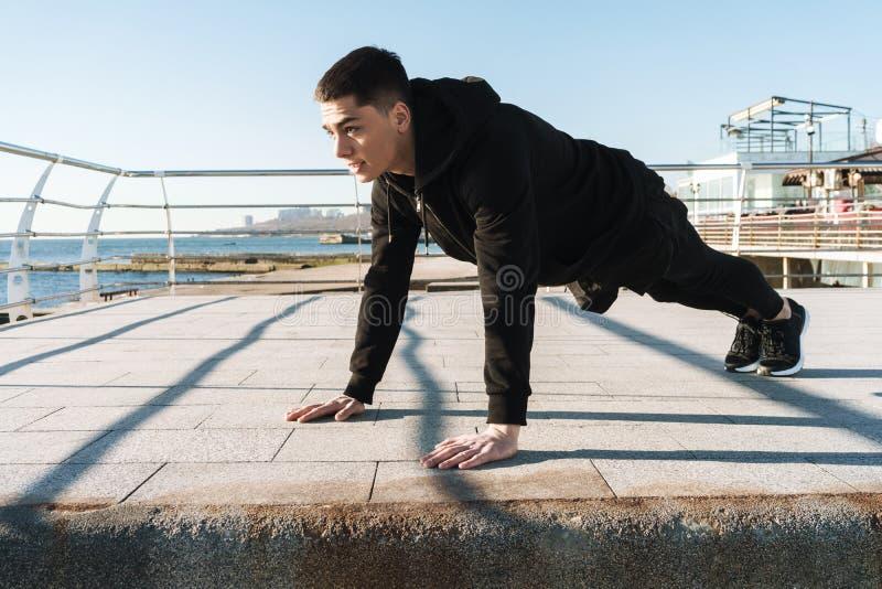 Foto del individuo europeo que hace pectorales en el piso durante entrenamiento de la mañana por la playa fotos de archivo libres de regalías