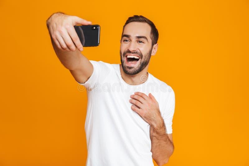 Foto del individuo europeo 30s en la ropa de sport que ríe y que toma el selfie en el teléfono celular, aislada sobre fondo amari imágenes de archivo libres de regalías