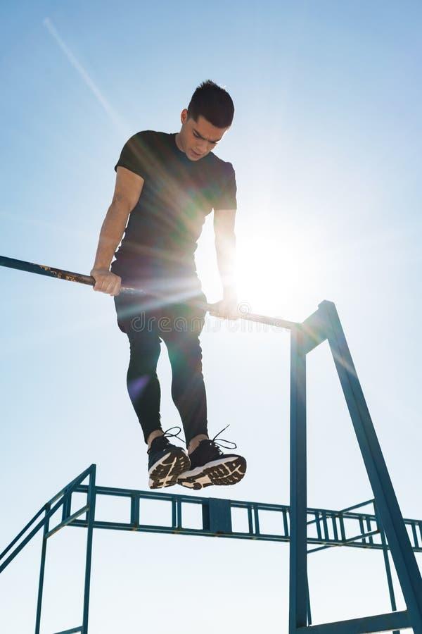 Foto del individuo fuerte que hace la acrobacia en barra gimnástica horizontal durante entrenamiento de la mañana por la playa fotografía de archivo libre de regalías