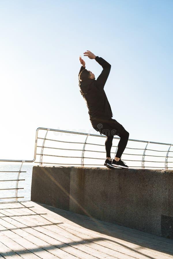 Foto del individuo fuerte 20s que hace la acrobacia y que salta durante entrenamiento de la mañana por la playa imagenes de archivo