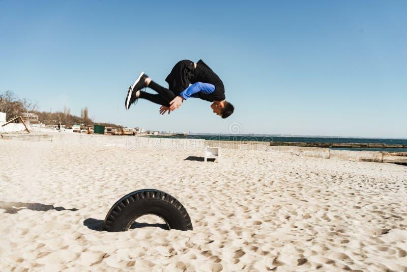 Foto del individuo intrépido que hace el parkour y que salta durante la acrobacia de la mañana por la playa fotografía de archivo