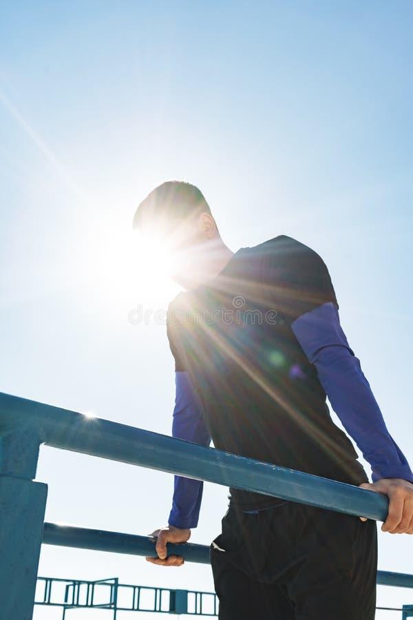 Foto del individuo joven que hace la acrobacia en barra gimnástica horizontal durante entrenamiento de la mañana por la playa imágenes de archivo libres de regalías