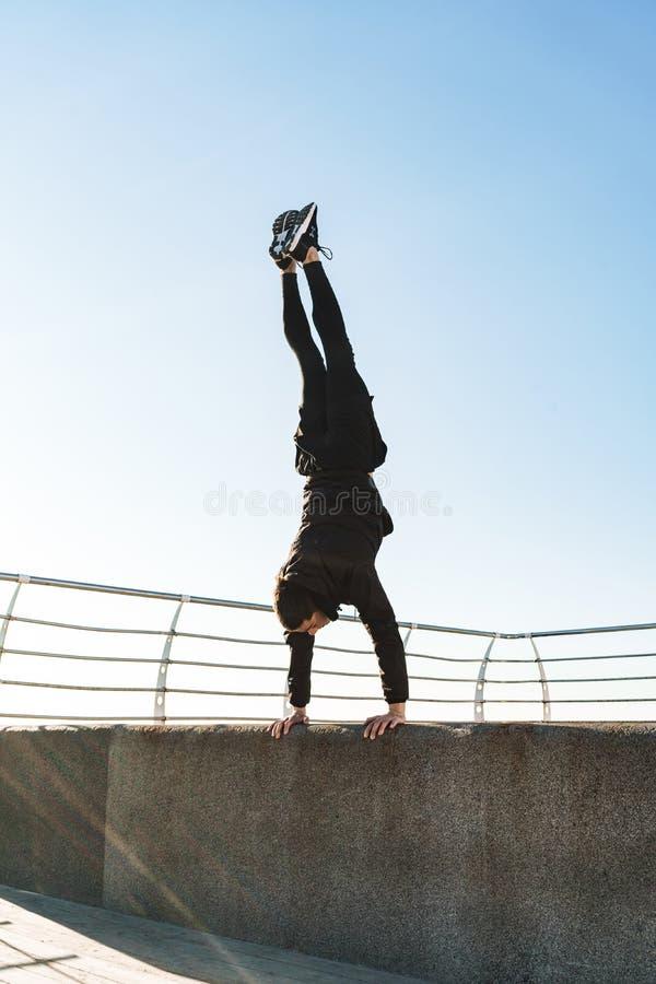 Foto del individuo joven que hace la acrobacia y que salta durante entrenamiento de la mañana por la playa fotos de archivo
