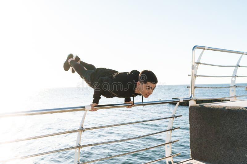 Foto del individuo muscular que hace la acrobacia y que salta durante entrenamiento de la mañana por la playa fotos de archivo libres de regalías