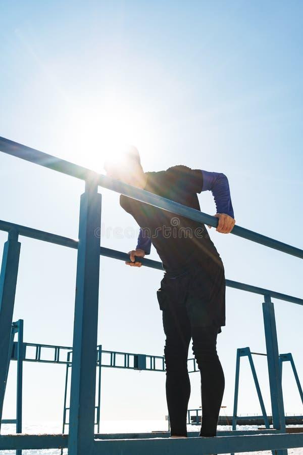 Foto del individuo sano que hace la acrobacia en barra gimnástica horizontal durante entrenamiento de la mañana por la playa fotos de archivo