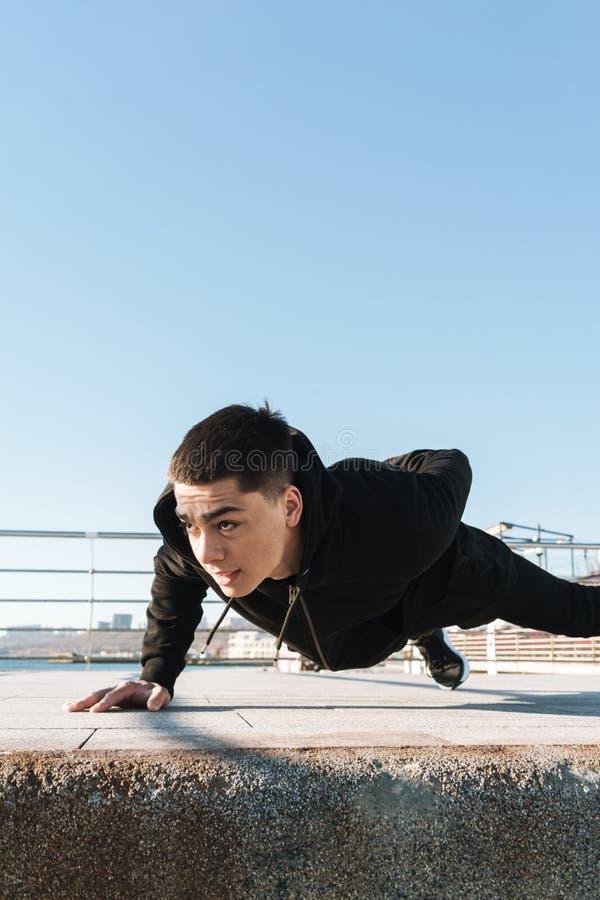Foto del individuo sano que hace pectorales en el piso durante entrenamiento de la mañana por la playa fotos de archivo