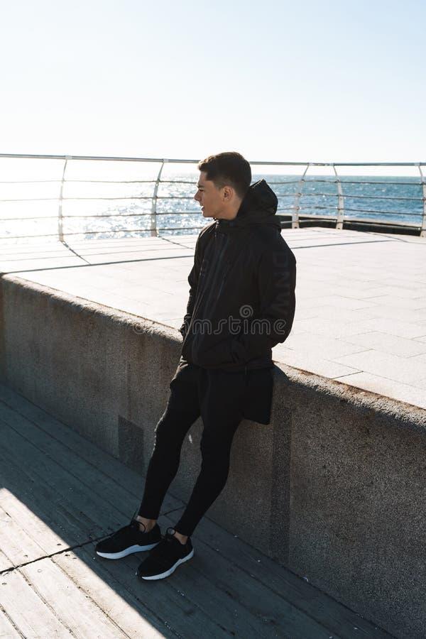 Foto del individuo satisfecho que camina a lo largo de paseo marítimo de madera por la playa durante entrenamiento de la mañana fotos de archivo libres de regalías