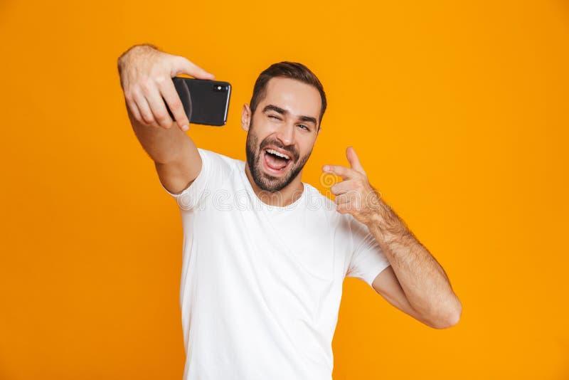 Foto del individuo satisfecho 30s en la ropa de sport que ríe y que toma el selfie en el teléfono celular, aislada sobre fondo am imagen de archivo libre de regalías