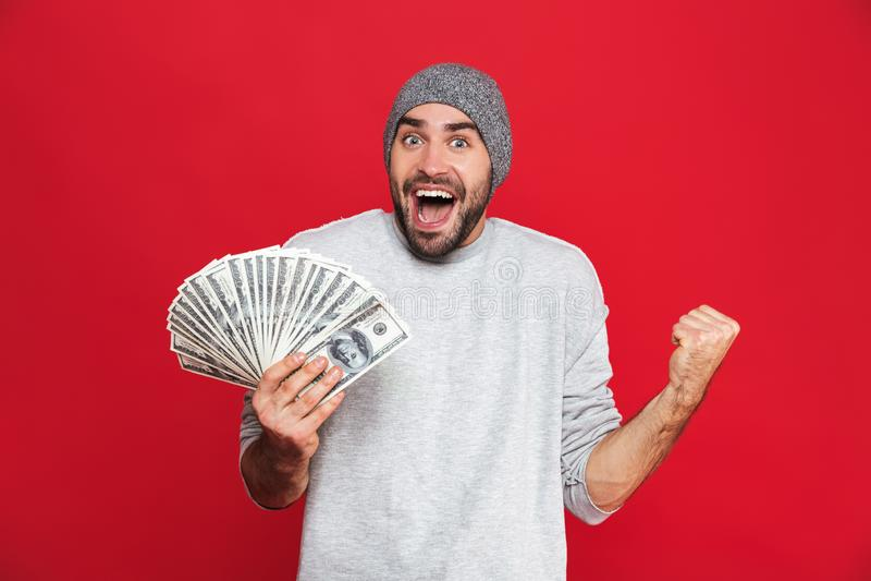Foto del júbilo europeo y de sostener del individuo el dinero del efectivo aislado sobre fondo rojo imagen de archivo