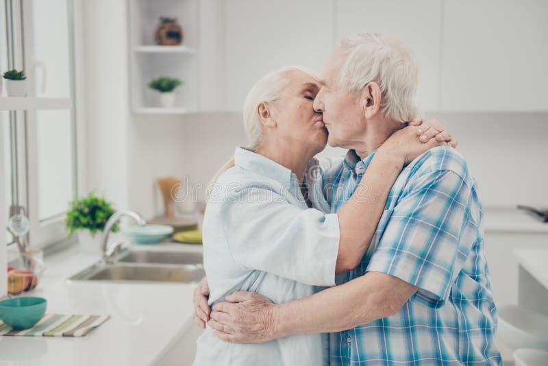 Foto del lato di profilo degli innamorati sposati che baciano il contenuto di tatto per godere della cucina della stanza di condi immagine stock libera da diritti