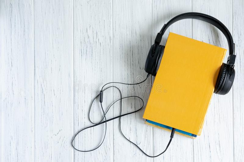 Foto del libro e delle cuffie collegati a  Audio libro Foto concettuale sull'argomento di apprendimento a distanza Ascoltando immagine stock