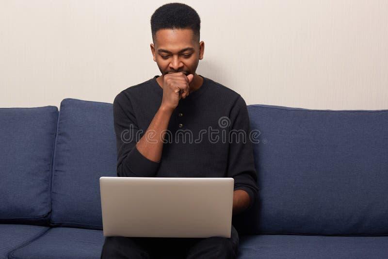 Foto del maschio bello pelato scuro stanco, lavorante al computer portatile, facendo uso di Internet, dello sbadiglio e dei sembr fotografie stock