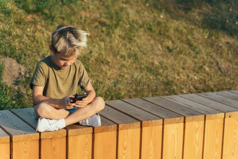 Foto del muchacho con las manos de los teléfonos que se sientan en la cerca de madera al aire libre imagenes de archivo