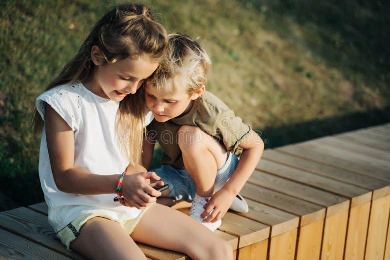 Foto del muchacho y de la muchacha con las manos de los teléfonos que se sientan en la cerca de madera al aire libre imagenes de archivo
