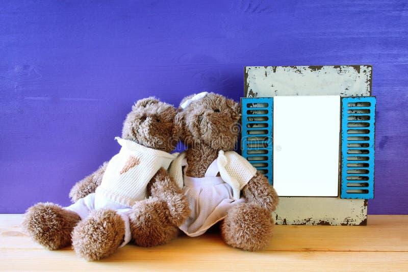 Foto del oso de peluche lindo de los pares al lado del marco vacío fotos de archivo libres de regalías