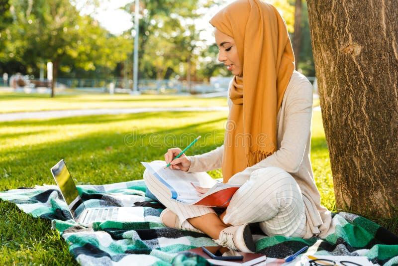 Foto del pañuelo que lleva de la muchacha árabe elegante que se sienta en la manta en parque verde foto de archivo libre de regalías