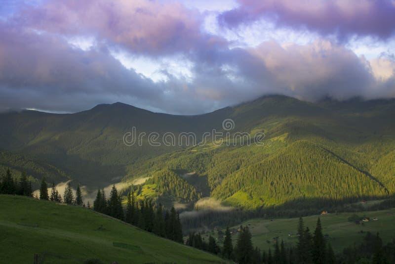 Foto del paisaje de la montaña en el verano debajo del cielo nublado hermoso Ucrania, Cárpatos, pueblo de Dzembronia fotos de archivo
