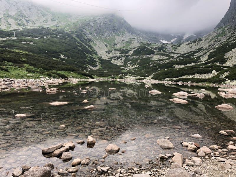 Foto del paisaje de las aguas de superficie rodeadas por las montañas imagen de archivo