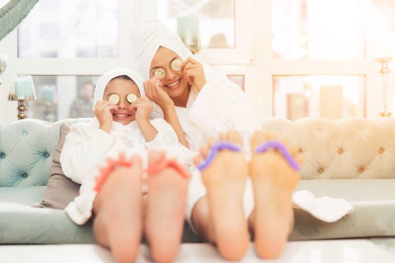 Foto del primer de la hija y de la madre con la esponja para la pedicura en los fingeres Leyeron las revistas en las albornoces b fotos de archivo