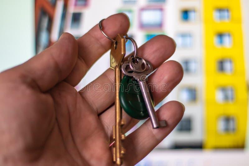 Foto del primer de la mano de un hombre que lleva a cabo las llaves a una nueva casa en el fondo de un edificio residencial moder fotos de archivo libres de regalías