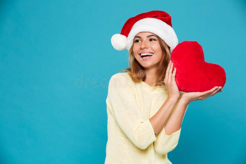 Foto del primer de la muchacha feliz en el sombrero amarillo de la blusa y del ` s de Papá Noel que lleva a cabo el corazón suave imágenes de archivo libres de regalías