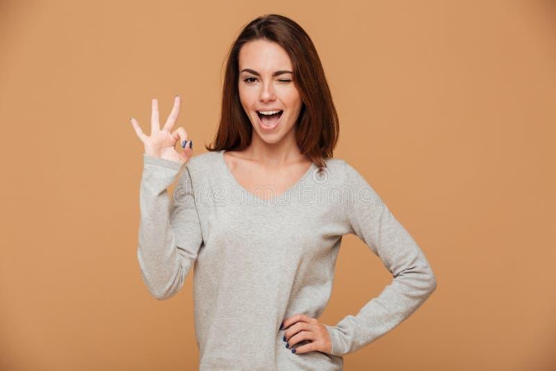 Foto del primer de la mujer morena joven divertida en la demostración gris de la blusa foto de archivo libre de regalías