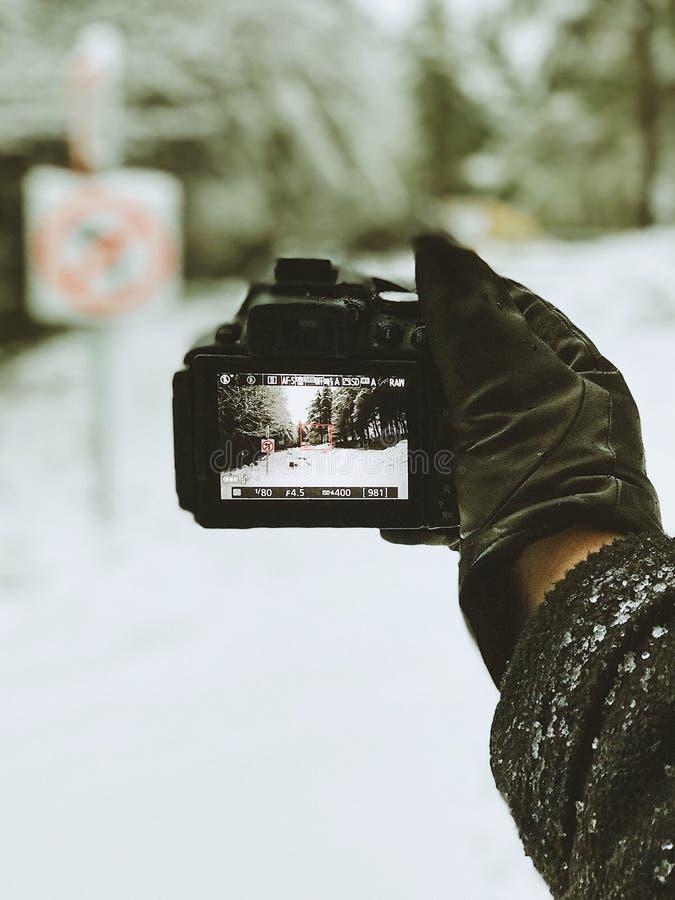Foto del primer de la persona que sostiene la cámara negra imagen de archivo libre de regalías