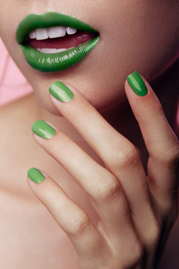 Foto del primer de labios y de clavos en maquillaje en colores pastel verde en fondo rosado Foto vertical fotos de archivo libres de regalías