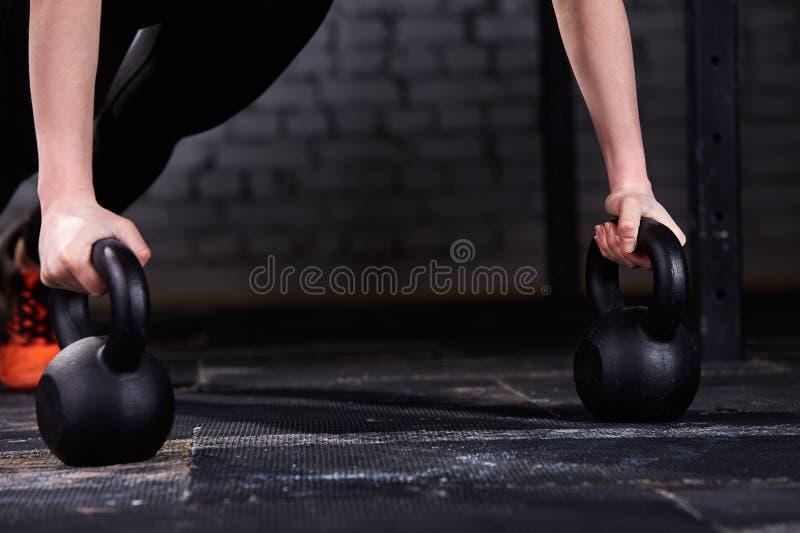 Foto del primer de las manos jovenes del ` s de la mujer del atleta mientras que hace pectorales en kettlebells contra la pared d imagenes de archivo