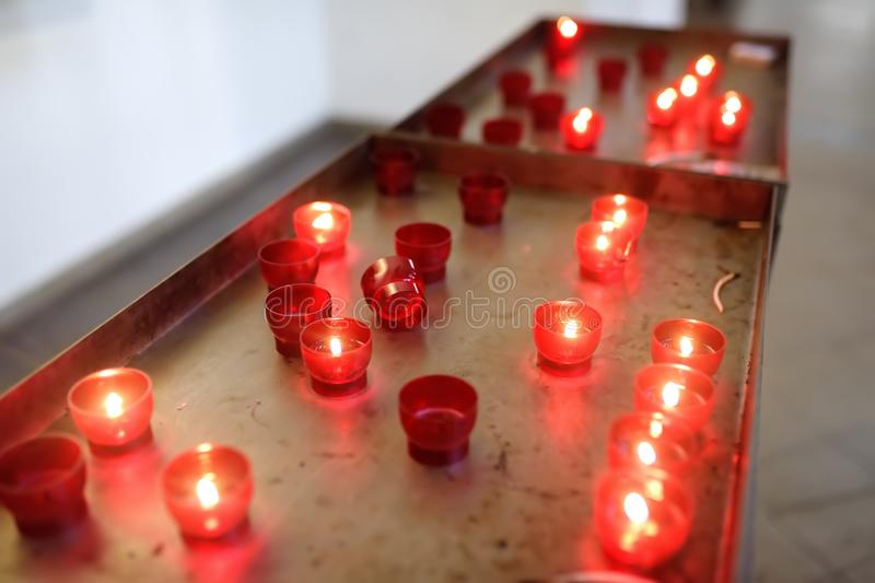 Foto del primer de las velas de la iglesia en lámparas transparentes rojas fotos de archivo libres de regalías