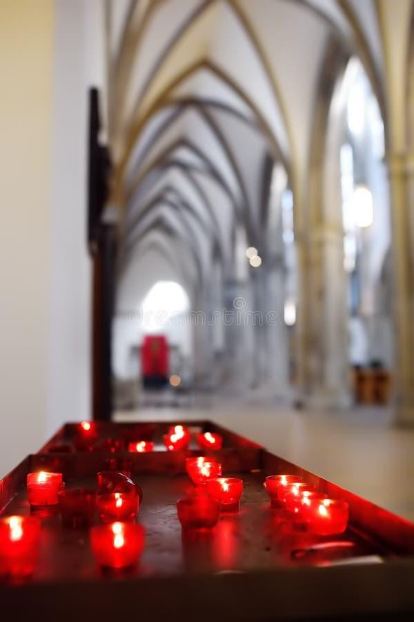 Foto del primer de las velas de la iglesia en lámparas transparentes rojas fotos de archivo