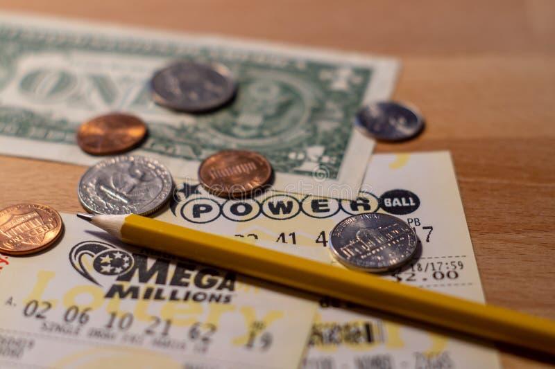 Foto del primer de los boletos de lotería de la bola y de Mega Millions del poder con el billete de dólar y las monedas foto de archivo libre de regalías
