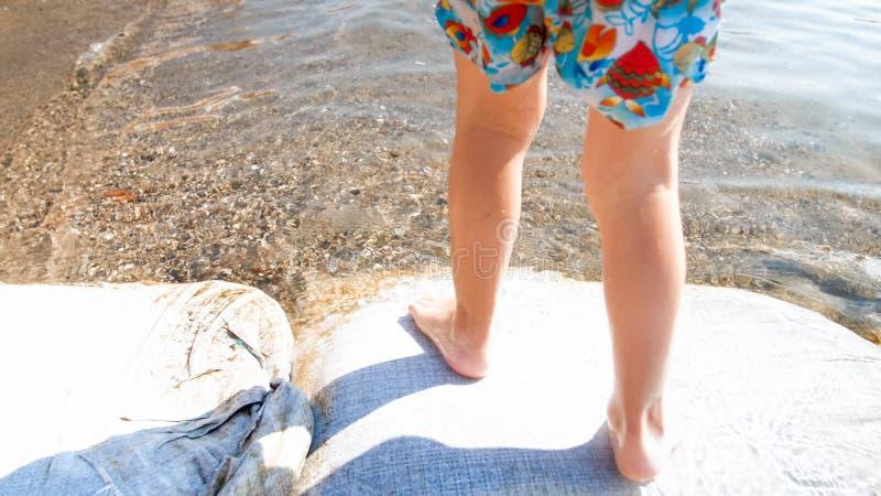 Foto del primer de los pequeños pies de los childs que caminan en la arena mojada en la playa del mar imagen de archivo
