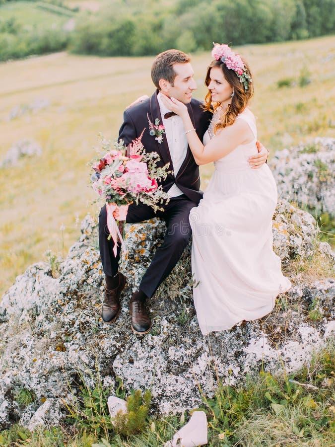 Foto del primer de los recienes casados alegres que se sientan en la piedra La novia está frotando ligeramente la mejilla del nov imagen de archivo libre de regalías
