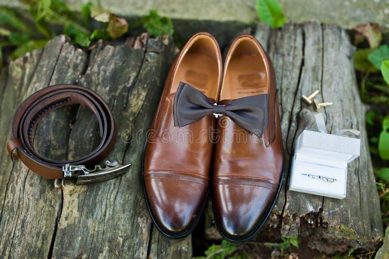Foto del primer de los zapatos, de las mancuernas, de la correa y de la corbata de lazo del ` s del novio encendido imagen de archivo libre de regalías