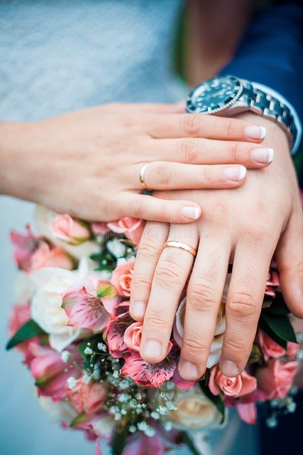 Foto del primer de manos de la novia y del novio con los anillos de bodas y el ramo fotos de archivo libres de regalías
