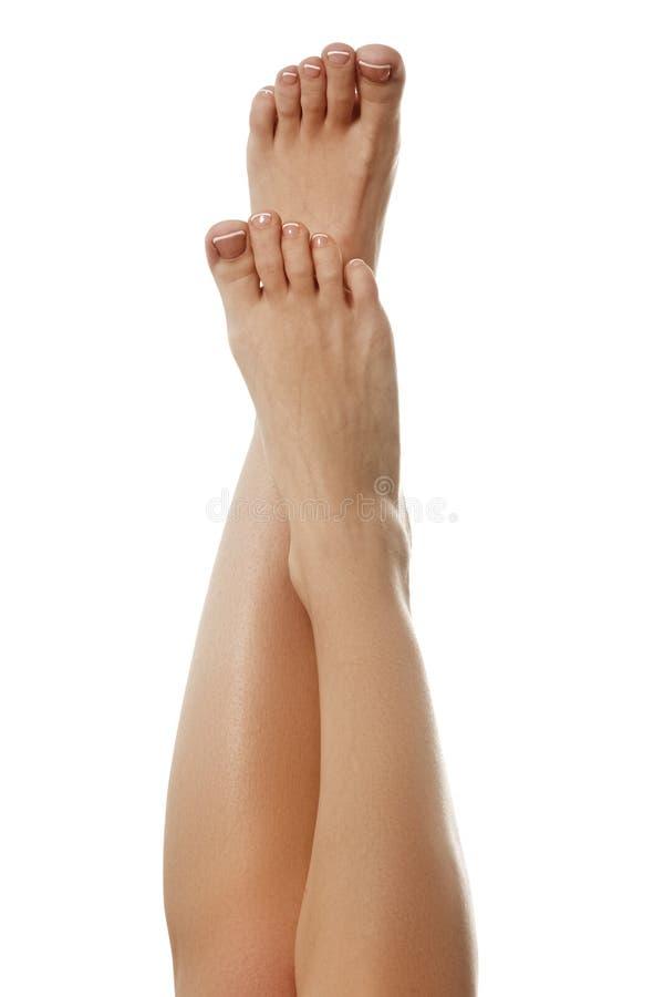 Foto del primer de pies femeninos con la pedicura francesa blanca en el nai imagen de archivo