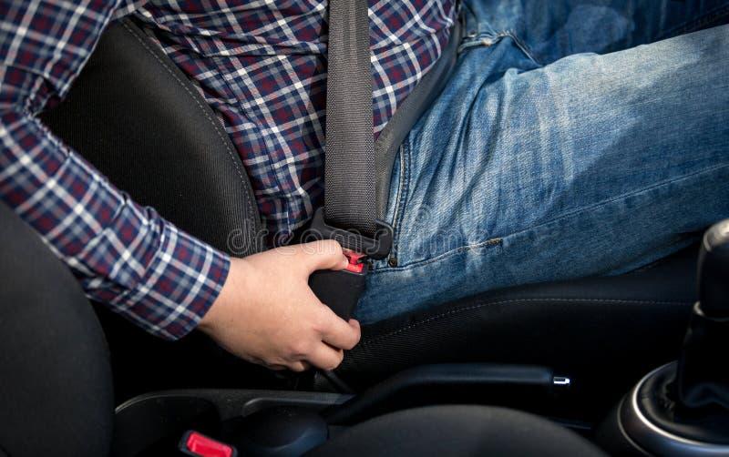 Foto del primer del asiento del hombre en asiento de conductores y la correa de la cerradura foto de archivo libre de regalías