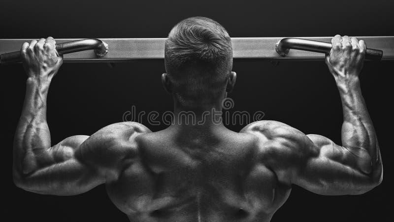 Foto del primer del individuo muscular atractivo del culturista que hace tirón foto de archivo libre de regalías