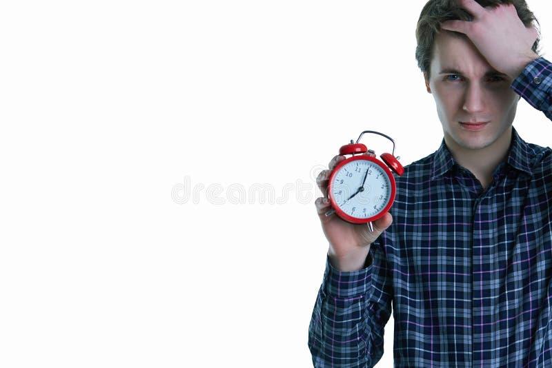 Foto del primer del hombre joven del trastorno con la mano en el pelo que sostiene el despertador rojo, aislada sobre el fondo bl fotos de archivo