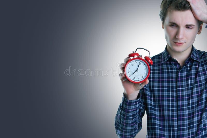 Foto del primer del hombre joven del trastorno con la mano en el pelo que sostiene el despertador rojo, aislada sobre fondo gris imágenes de archivo libres de regalías