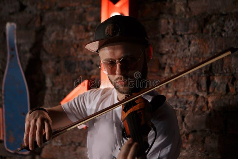 Foto del primer del hombre que toca el violín eléctrico fotos de archivo libres de regalías